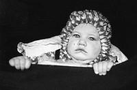 Portrait of baby looking over edge of pram,