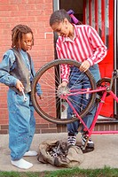 Mother and young son mending bicycle at front of house