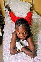 Young patient with bandaged hand lying on bed on children´s medical ward,