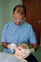 Dental examination or check up, with dentist wearing protective eyewear