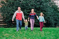 Family group walking in park holding hands