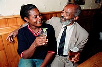 Man and woman sitting at table in pub drinking pints of beer and smiling at each other,