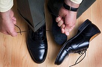 Businessman tying his shoes