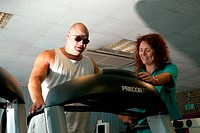 Access to services, Fitness Instructor and disabled man in the gym, using Treadmill,