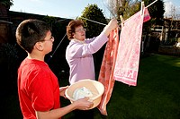 Grandmother pegging washing on the clothes line with her grandson helping