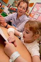 Paediatric patient in Hospital schoolroom reading to ward teacher,