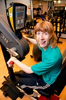 Woman using upper body ergometer at an inclusive fitness gym