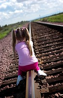 Girl sitting on railroad tracks