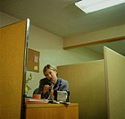 Businesswoman sitting in office, talking on telephone
