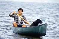 Man with dog canoeing on lake, portrait