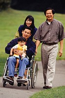 Family walking in park, father in wheelchair
