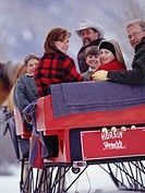 Family riding in sleigh, portrait