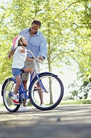 Father teaching daughter (4-5) to ride bicycle in park