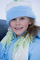 Young girl (6-7) with missing tooth in snow, portrait