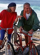 Man and woman standing with bikes at seashore