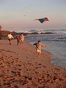 Family with two children  (6-7), (8-9), flying kite on beach