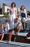 Family with two children (10-11), (14-15), posing on yacht, portrait