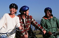 Three women standing with bicycles on pier