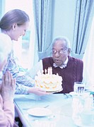 Senior man blowing out candles on birthday cake, in restaurant