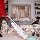 Woman vacuuming floor in living room, husband lying on sofa