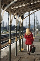 Woman walking on train platform, rear view