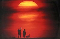 Silhouette of couple with dog, man aiming, sunset