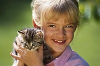 Girl (6-7) holding cat, close-up, portrait, smiling
