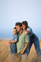 Family with daughter (6-7) in field looking away, smiling