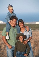Family with two children (6-9) in field, smiling