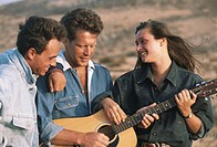 Woman standing with two men in desert, man playing guitar