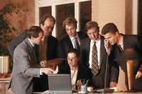 Business people looking at laptop screen, man using telephone