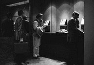 Businessmen using public phone (B&W)