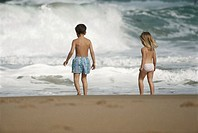 Boy and girl (2-5) standing on beach, rear view