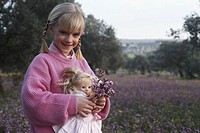 Girl (6-7) holding doll and flower standing in field