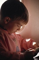 Boy (4-5) reading book, close-up