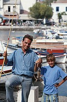 Father and son (6-9) with fish at harbour, portrait