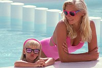 Mother with daughter (4-5) leaning on edge of swimming pool