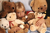 Girl (6-7) lying between soft toys on bed, portrait