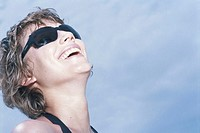 Young woman wearing sunglasses, laughing