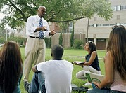 Male professor giving lecture to group of young adults outdoors