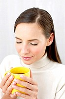 Woman smelling an aromatic cup of coffee