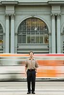 Man standing in urban road, portrait (blurred motion)