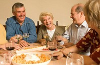 Group of mature adults sitting at table, drinking wine and laughing