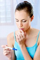 Woman looking worried with her pregnancy test results