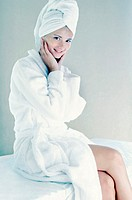 Woman in bathrobe with towel wrapped hair