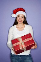 Young woman wearing Santa hat, holding present, smiling, portrait