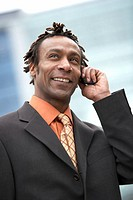 Businessman using mobile phone, looking up, smiling, close-up