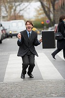 Businessman celebrating on zebra crossing, holding briefcase, portrait