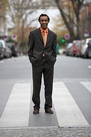 Businessman on zebra crossing, hands in pockets, smilng, portrait