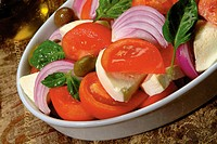 Tomatoe salad with olives, basil and red onions